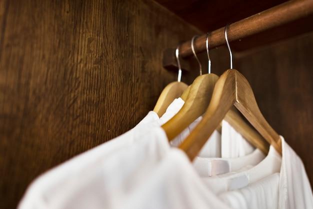 Weiße kleidung, die in einer garderobe hängt