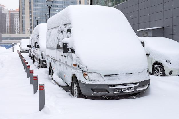 Weiße kleinbusse schneite während eines schneesturms im winter auf dem parkplatz.