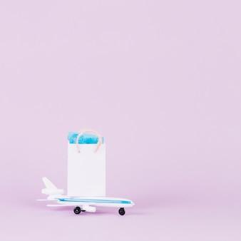 Weiße kleine einkaufstasche über spielzeugflugzeug gegen rosa hintergrund