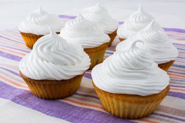 Weiße kleine kuchen auf der gestreiften leinenserviette