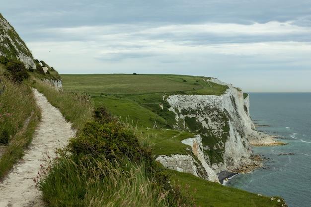 Weiße klippen von dover bedeckt im grünen unter einem bewölkten himmel in großbritannien