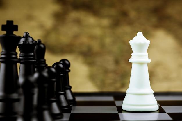 Weiße königin-schachfiguren begegnen schwarzen feinden auf einem schachbrett. - geschäftssieger und kampfkonzept.