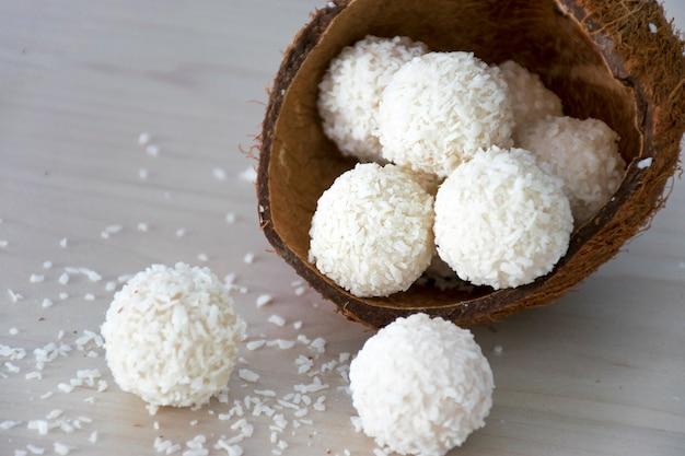 Weiße kokosnussbonbonbällchen der hausgemachten süßigkeiten in der nussschale.