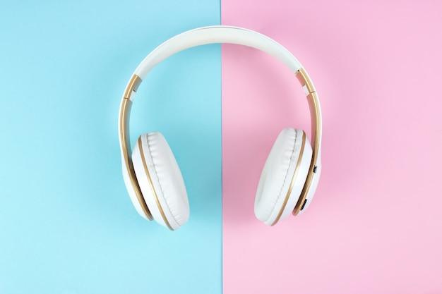 Weiße kopfhörer auf blauem rosa pastellhintergrund.