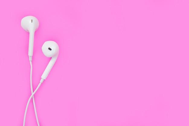Weiße kopfhörer auf rosa mit kopienraum und beschneidungspfad. flach liegen. ansicht von oben.
