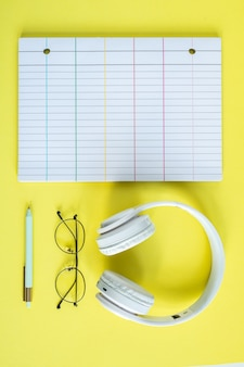 Weiße kopfhörer, brillen, stift und linierte seite des notizbuchs über gelbem hintergrund