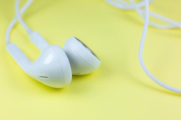 Weiße kopfhörer, die auf dem gelben hintergrund liegen. modernes musikkonzept. audio-technologie. nahaufnahme foto.