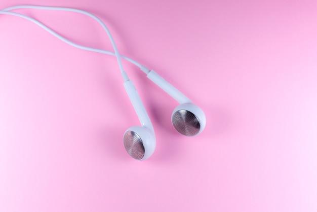 Weiße kopfhörer, die auf dem rosa hintergrund liegen. modernes musikkonzept. audio-technologie. nahaufnahme foto.