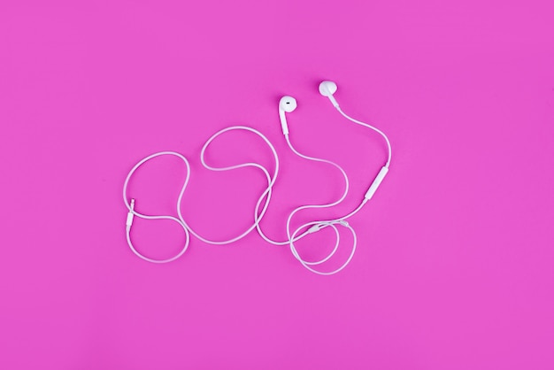 Weiße kopfhörer für musik auf rosa