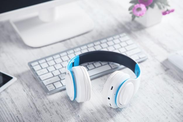 Weiße kopfhörer mit computer. business desk