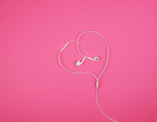 Weiße kopfhörer mit einem kabel auf rosa