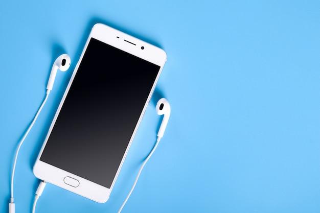 Weiße kopfhörer und smartphone auf blauem tisch