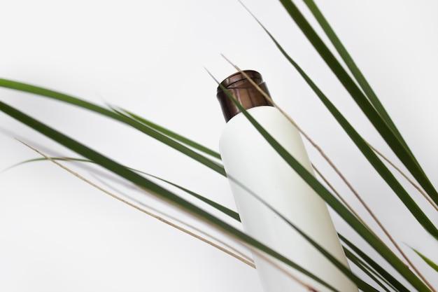 Weiße kosmetikflasche in den blättern auf weißem hintergrund