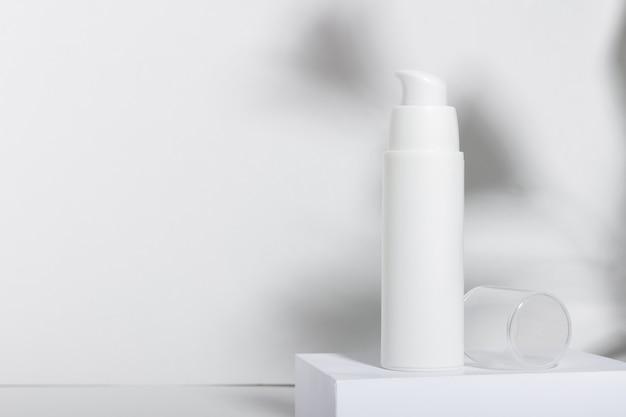 Weiße kosmetiktube für creme, lotion, serum oder gesichtsmaske auf dem laufsteg mit blattschatten. professionelle kosmetik für die hautpflege. bio-kosmetik.