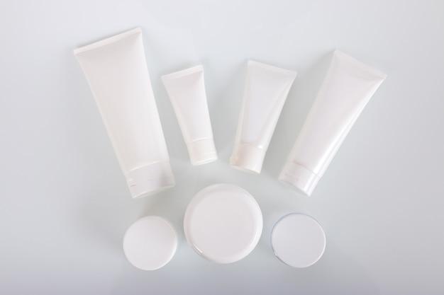 Weiße kosmetische gefäße und schüssel auf weiß