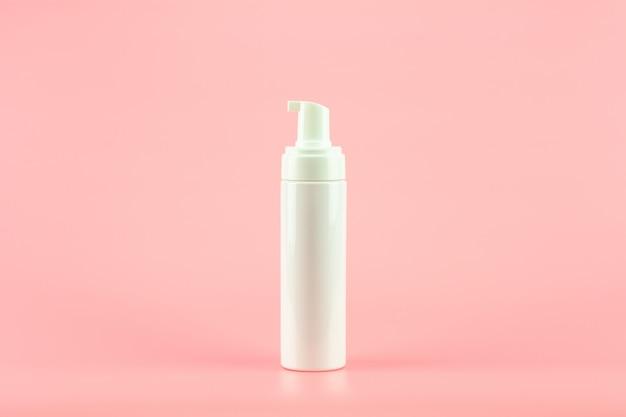 Weiße kosmetische lotionsplastikflasche auf rosa hintergrund.