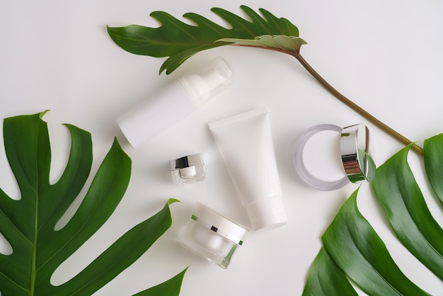 Weiße kosmetische produkte und grünblätter auf weißem hintergrund. branding-mock-up-konzept.