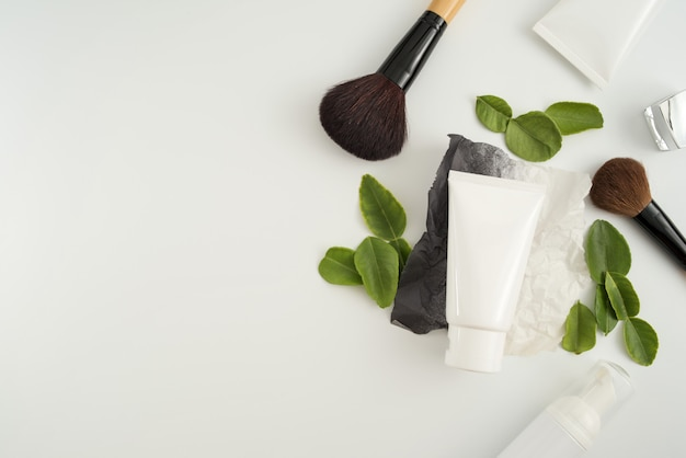 Weiße kosmetische produkte und grünblätter auf weißem hintergrund. branding-modell-konzept.