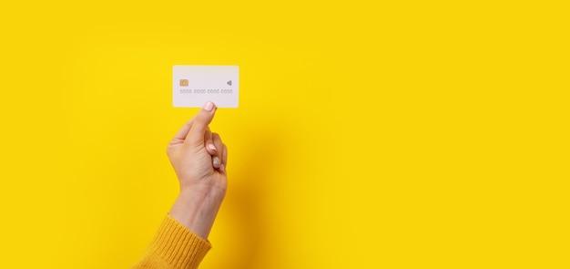 Weiße kreditkarte in der hand über gelbem hintergrund, panoramabild