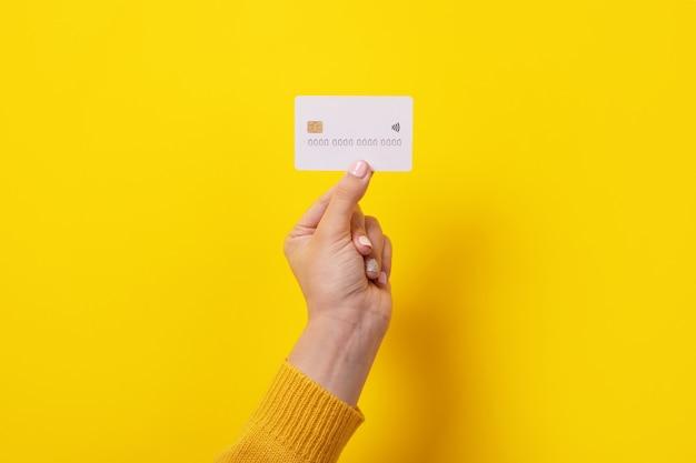 Weiße kreditkarte in weiblicher hand, karte mit elektronischem chip über gelbem hintergrund