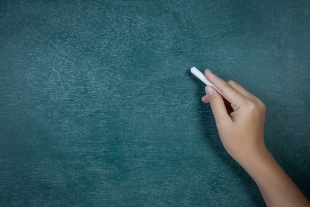 Weiße kreide in der hand vor dem rückenbrett