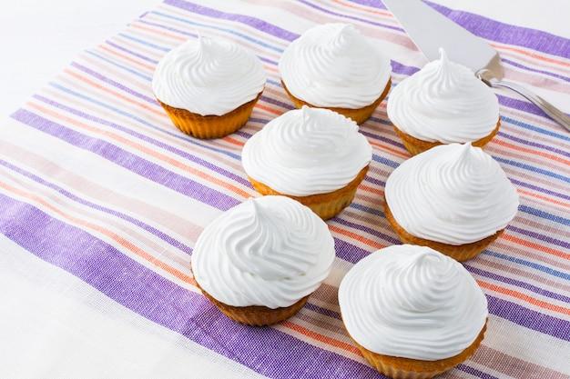 Weiße kuchenreihe auf der leinenserviette