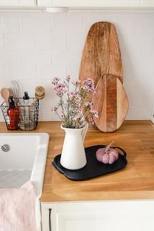 Weiße küche im modernen skandinavischen stil mit einem strauß lila blumen in einem krug und verschiedenen küchenutensilien. gemütliches wohnkonzept