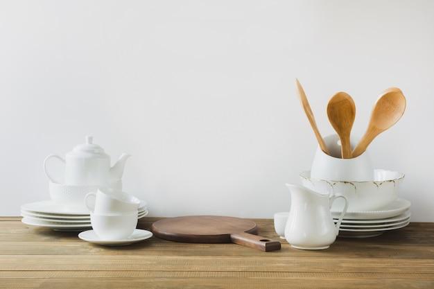 Weiße küchengeräte, geschirr und anderes unterschiedliches weißes material für das dienen auf weißem hölzernem brett.