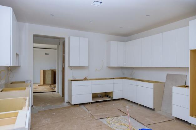 Weiße küchenschränke aus holz mit moderner installationsbasis