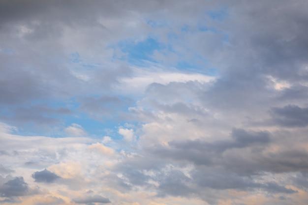 Weiße kumuluswolken auf einem blauen himmel an einem sommerabend.