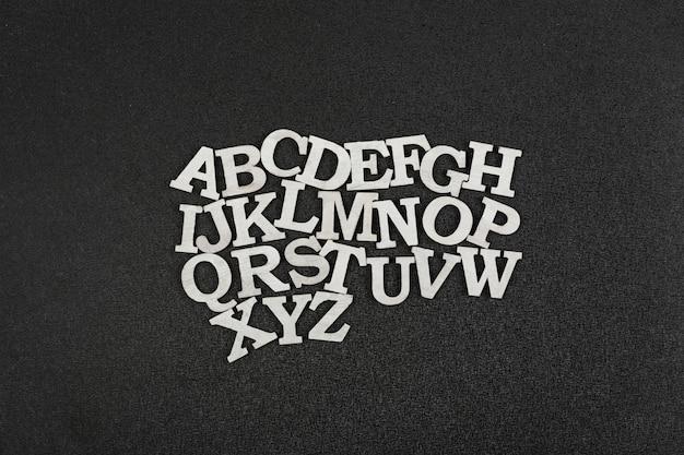 Weiße lateinische buchstaben auf schwarzem raum. kindergarten alphabet.