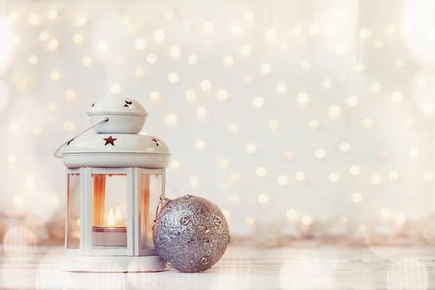 Weiße laterne mit kerze und silberner kugel - weihnachtsdekoration.