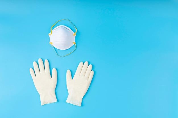 Weiße latexhandschuhe und maske. schutz-coronavirus-konzept. mit angemessenem schutz besiegen sie den virus.