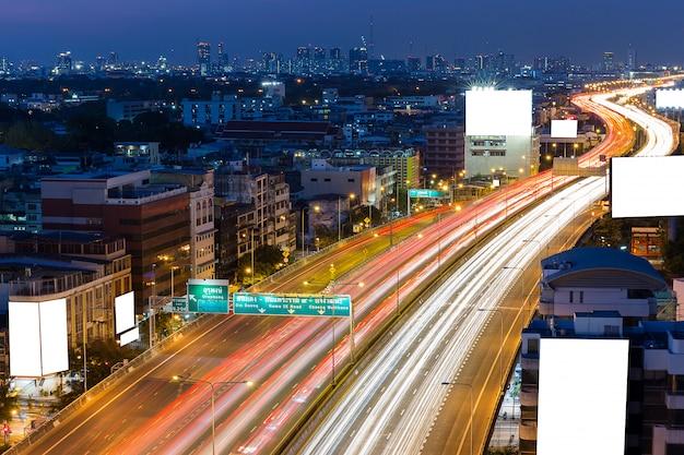 Weiße leere anschlagtafel auf der autobahn in der dämmerungszeit in im stadtzentrum gelegenem bangkok thailand