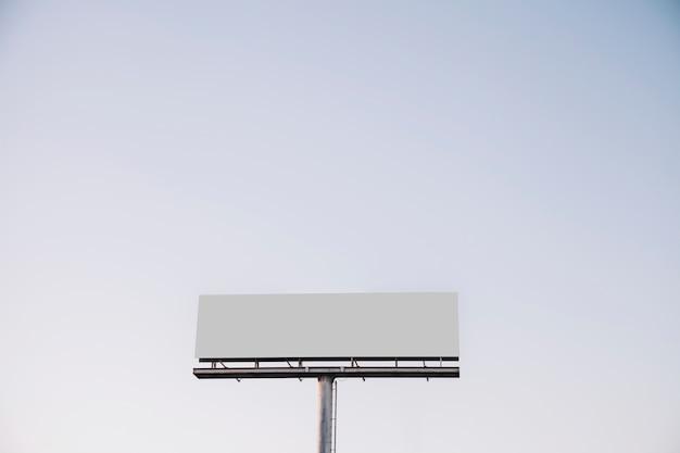 Weiße leere anschlagtafel gegen blauen himmel