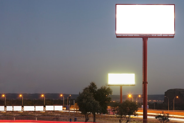 Weiße leere anschlagtafel über der belichteten landstraße während der nacht