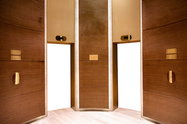 Weiße leere aufzugstüren auf holzraum mit goldener materialdekoration