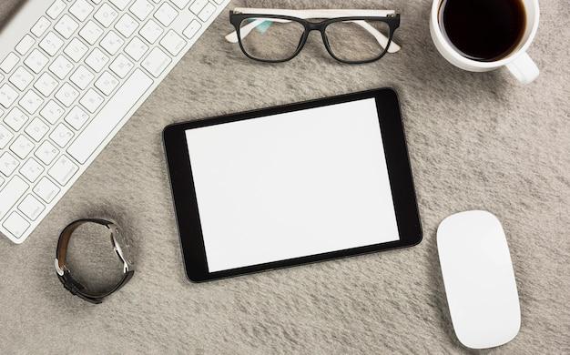 Weiße leere digitale tablette mit kaffeetasse; schauspiel; maus; tastatur und armbanduhr auf grauem schreibtisch