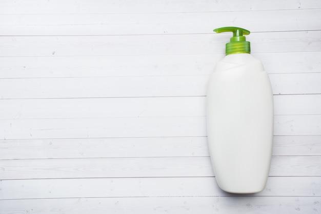 Weiße leere flüssige flasche auf weißem hölzernem hintergrund.