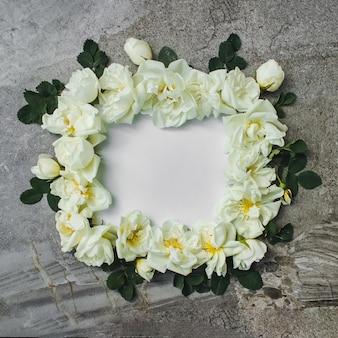 Weiße leere karte mit pastellrosenblumen auf grauem marmorhintergrund. geburtstagsgrußkarte. muttertag. platz für text. natur-konzept. flach liegen.