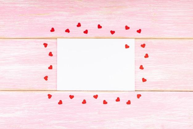 Weiße leere karte mit roten konfettiherzen auf rosa hölzernem hintergrund