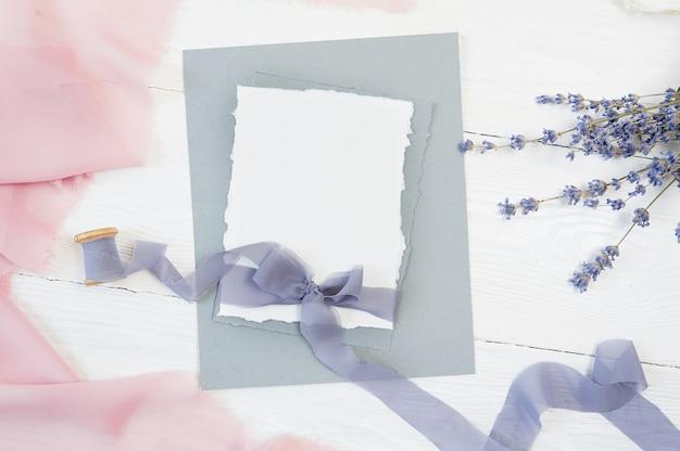 Weiße leere kartenbandschleife auf einem hintergrund des rosa und blauen gewebes mit lavendelblume