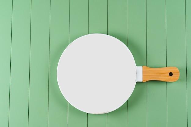 Weiße leere keramische nahrungsmittelpfanne auf grünem holztisch. weißer teller auf dem tisch