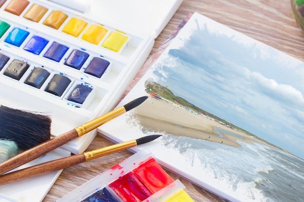 Weiße leere leinwand mit pinseln und aquarellfarben auf dem tisch