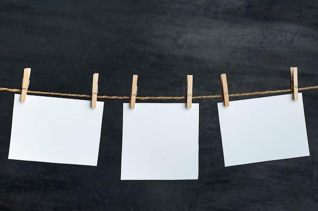 Weiße leere papiernotizen hängen mit wäscheklammern am seil