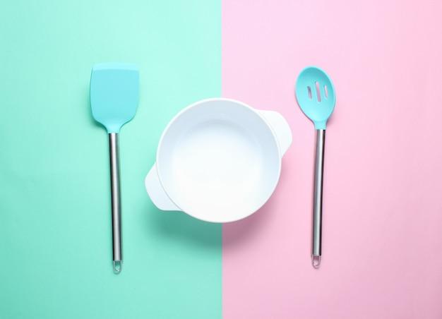 Weiße leere schüssel mit schneebesen mit spatel zum kochen, kelle auf pastellhintergrund. draufsicht, minimalismus