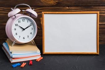 Weiße leere Tafel; Wecker; Wäscheklammer und Notizbücher auf schwarzem Schreibtisch