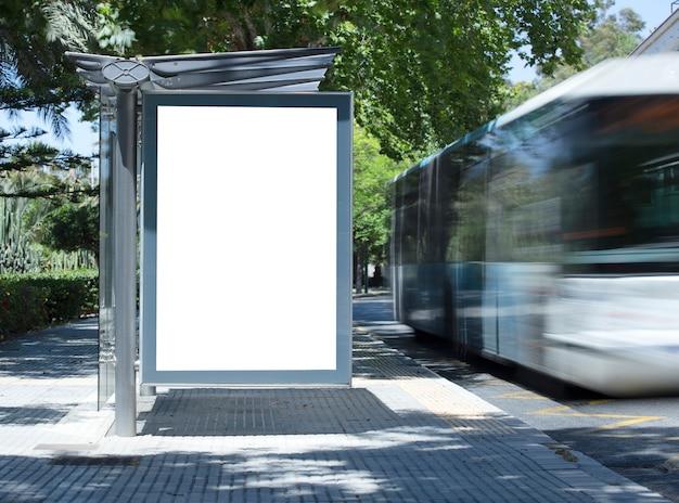 Weiße leere vertikale werbetafel an der bushaltestelle auf der stadtstraße im hintergrund von bussen und ro