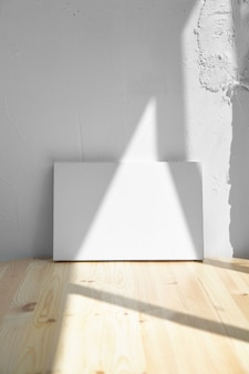 Weiße leinwand des leeren modells auf holztisch und weißer wand mit licht und schatten