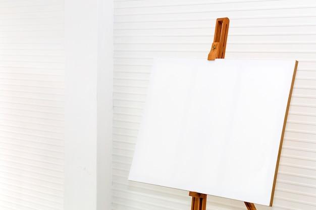 Weiße leinwandmalerei auf hölzernem zeichnungsstand zu kreativem für design und dekoration.